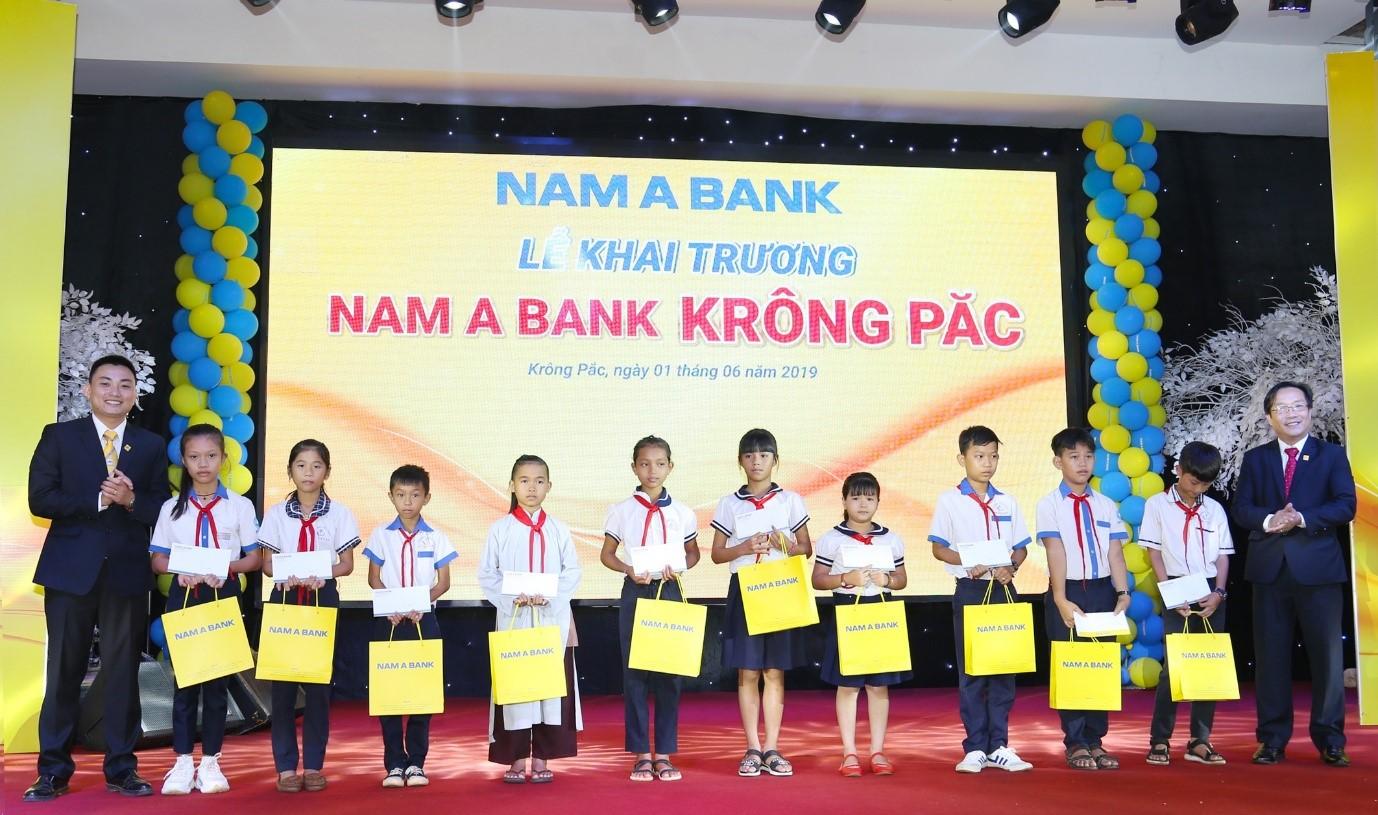 Ông Võ Anh Tú – Giám đốc Nam A Bank Đắk Lắk (bên phải) và Ông Vũ Xuân Phúc – Giám đốc Nam A Bank Krông Păc (bên trái) trao học bổng cho các em học sinh nghèo vượt khó.