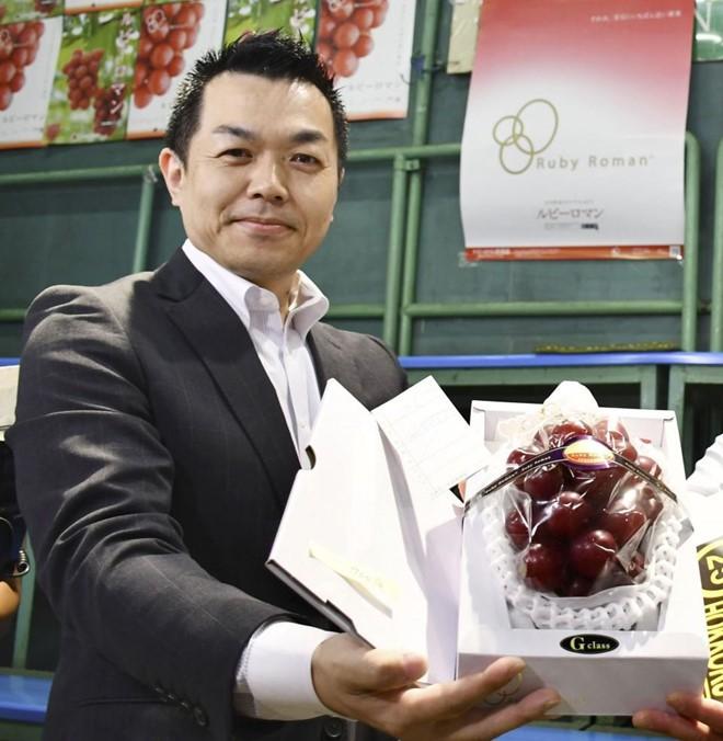 Ông Takashi Hosokawa và chùm nho trị giá 11.000 USD. Ảnh: Kyodo.