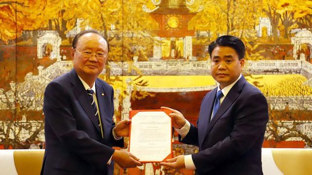 Chủ tịch UBND thành phố Hà Nội Nguyễn Đức Chung (phải) trao giấy chứng nhận đầu tư cho ông Lee Dae Bong, Chủ tịch Charmvit.