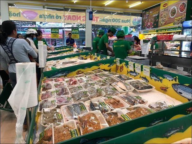 Gian hàng tươi sống của Bách hoá Xanh, phía xa là nhân viên đang làm thịt cá.