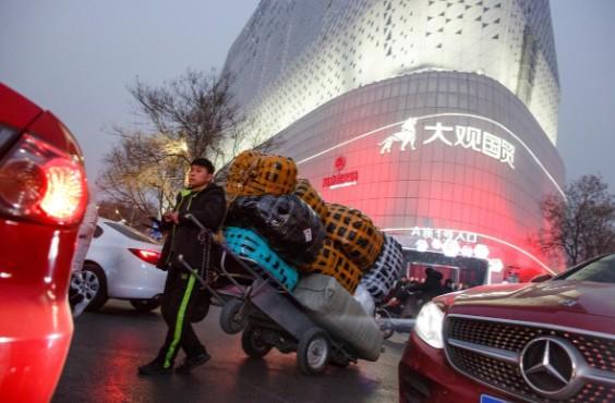 Một người đẩy hàng phía ngoài một trung tâm bán sỉ ở thành phố Trịnh Châu. Ảnh: Reuters.